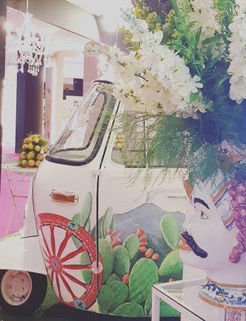 In questa foto un giardino decorato per un matrimonio in stile siciliano con una moto ape decorata con fiori bianchi dietro ad un vaso a forma di testa di moro