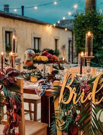 """In questa foto il tavolo degli sposi decorati in stile Boho Chic con palme e fiori rossi e gialli. Dietro le sedie degli sposi sono appese le scritte""""Bride"""" e """"Groom"""""""