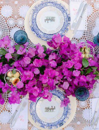 In questa foto una mise en place elegante nei colori del fuxia delle bouganville usate come runner floreale e del blu dei piatti in ceramica