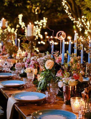 In questa foto una mise en place in stile Boho Chic su un tavolo imperiale in legno. Il runner è realizzato con candele azzurre, fiori colorati e vasetti luminosi. L'allestimento è completato con piatti azzurro polvere