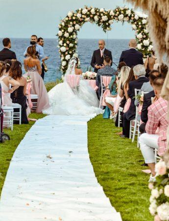 In questa foto due sposi in fondo durante la celebrazione del rito civile. Lungo il corridoio è presente un tappeto bianco fino ad un arco a forma di cuore di fiori e foglie