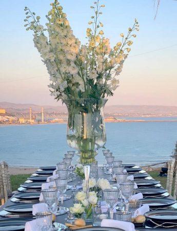 In questa foto un mise en place elegante vista mare nei toni del blu e del bianco. Al centro del tavolo è presento un grande vaso di cristallo con fiori di delphinium bianco