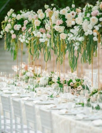 In questa foto un allestimento di nozze romantico nei colori del bianco, rosa e verde. Piccoli vasetti di fiori e foglie vengono usati come runner floreali e le stesse composizioni, più grandi e sospese, vengono usate come centrotavola