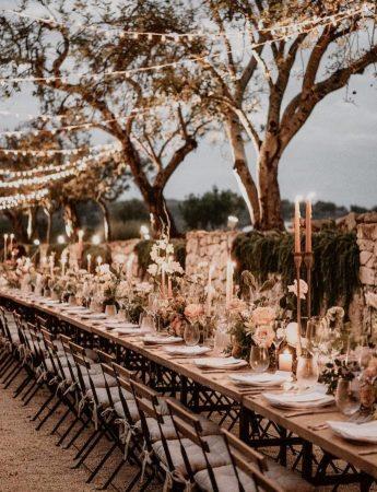 In questa foto un allestimento di nozze in stile Boho Chic con tavoli e sedie in legno senza tovagliato. Composizioni di rose rosa vengono usate come centrotavola insieme a candele lunghe