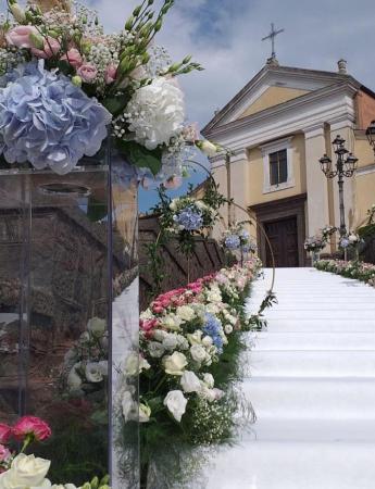 In questa foto l'allestimento della scalinata di una chiesa per un matrimonio religioso. La scalinata e rivestita da un tappeto bianco mentre sui bordi sono disposti fiori bianchi e fuxia e ortensie azzurre