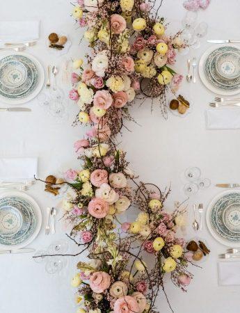 In questa foto la mise en place di un ricevimento di nozze vista dall'alto. Il tavolo è decorato con un centrotavola floreale disposto a serpentina nei colori del giallo e rosa e rametti secchi. I piatti sono in porcellana stile Richard Ginori e le posate sono in argento