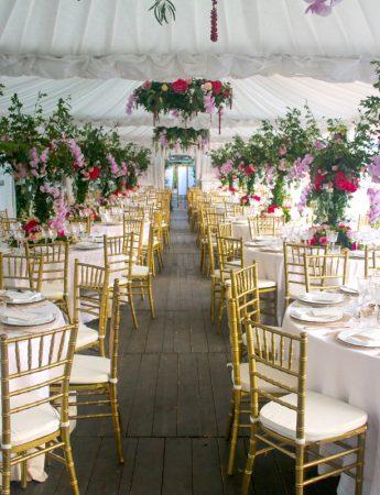 In questa foto l'allestimento di un ricevimento di nozze con gazebi e tendaggi. I tavoli, disposti lasciando spazio ad un corridoio centrale, sono decorati con tovaglie bianche, sedie colore oro e centro tavola floreali nei colori del rosso porpora e del verde