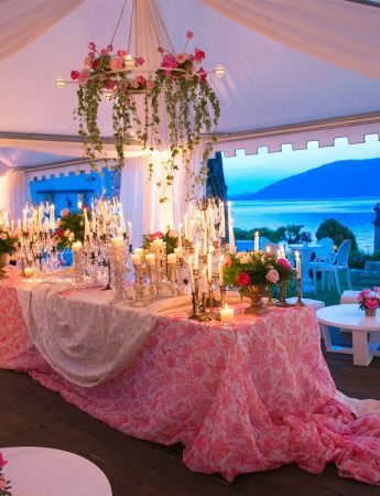 In questa foto l'allestimento di un ricevimento di nozze sotto tendaggi bianchi e su un prato. Al centro un grande tavolo ospita un buffet. È decorato con una tovaglia damascata nei colori del rosso e del bianco, coprimacchia bianchi e fiori rossi e verdi. Il tavolo è sormontato da un lampadario decorato con gli stessi fiori