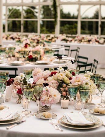In questa foto l'allestimento di un ricevimento di nozze diurno in una veranda di campagna. Come centrotavola sono usati fiori rosa, bordeaux e verdi. I piatti usati sono di colore tortora abbinati a sedie marrone scuro