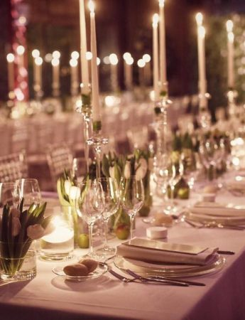 In questa foto una mise en place total white su tavoli imperiali fotografata alla luce delle candele. Vasetti con tulipani bianchi decorano il tavolo insieme a candelabri con candele alte illuminate