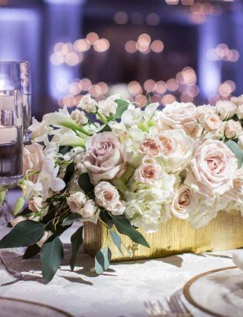 In questa foto una mise en place per un ricevimento di nozze serale nei toni del bianco, oro e rosa cipria. Una composizione floreale in un vaso rettangolare è usata come centrotavola