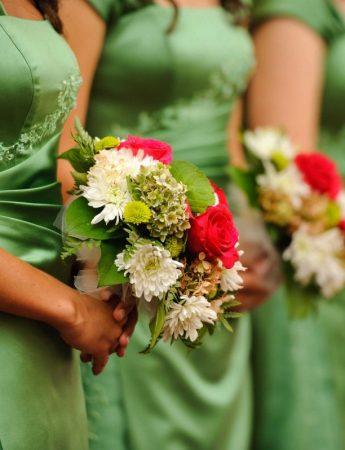 In questa foto 3 damigelle d'onore con un abito verde brillante tengono tra le mani bouquet di girasoli bianchi e rossi
