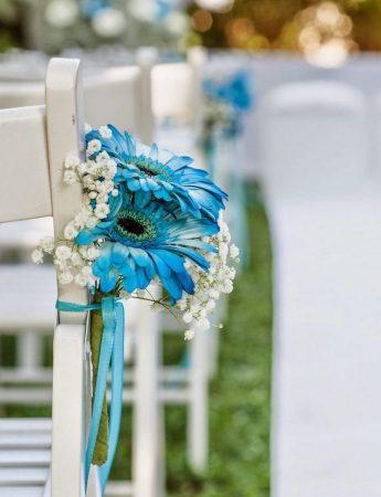 In questa foto il dettaglio di un allestimento per un rito civile nei colori bianco e azzurro. Alle sedie sono legati piccoli bouquet di girasoli azzurri e velo da sposa