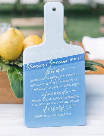 In questa foto il dettaglio di un menù stampato su un piccolo tagliere in legno dipinto in bianco e azzurro