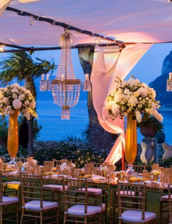 In questa foto un tavolo imperiale di un ricevimento al tramonto a Capri. I colori scelti sono il bianco dei fiori contenuti nei vasi in oro, l'altro colore scelto e usato anche per posate e sedie