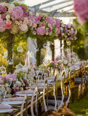 In questa foto un ricevimento di nozze allestito su un prato. Un tavolo imperiale si estende su tutta la lunghezza ed è decorato con alti centrotavola di fiori rosa posti in vasi trasparenti e alla base. Dai fiori scendono sfere trasparenti. Sedie colore coloro completano l'allestimento