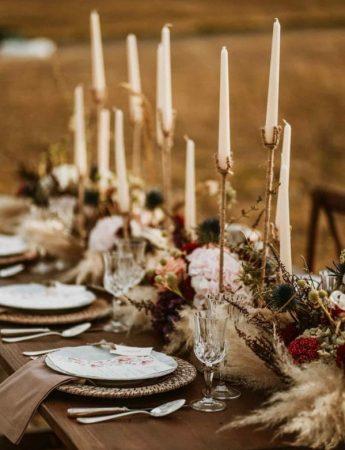 In questa foto una mise en place in stile Boho Chic per un ricevimento di nozze su un campo di grano. Un tavolo imperiale di legno visto in obliquo è decorato con candele alte e bianche, fiori rossi e sottopiatti in paglia