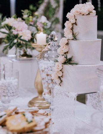 In questa foto uno sweet table decorato nei toni del bianco e del rosa cipria. Sul tavolo a piani sono disposti la wedding cake deocrata con rose rosa e biscotti di pasta frolla
