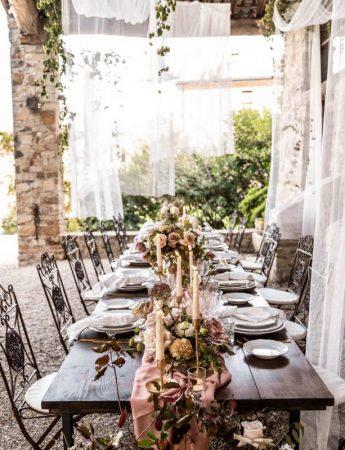 In questa foto un allestimento di nozze in stile Shabby Chic in campagna. Un runner decorato con fiori rosa e bianchi decora un tavolo di legno nudo. Su entrambi i lati sono disposti i piatti. Le sedie usate sono in ferro battuto