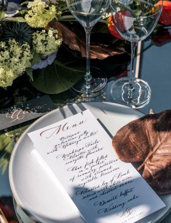 In questa foto una mise en place ripresa in obliquo realizzata su una tavola a specchio. Su un piatto bianco è poggiato un menù abbinato ad una foglia usata come segnaposto. Sono abbinate posate colore oro