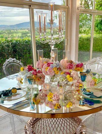 In questa foto un'esclusiva mise en place firmata da Erika Morgeracon tavolo specchiato ed lussureggianti composizioni floreali colorate