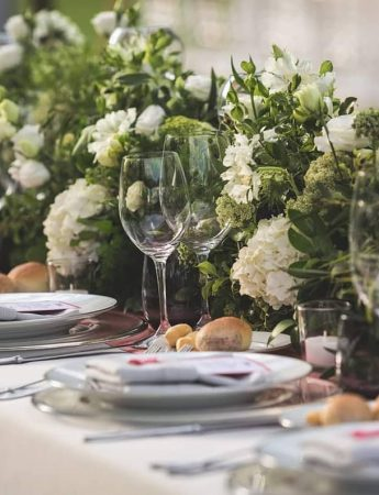 In questa foto un tavolo imperiale arricchito con un rigoglioso decoro floreale dai toni del verde
