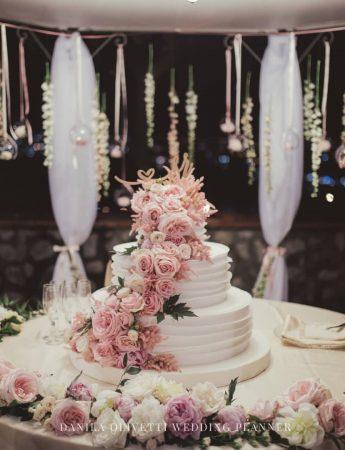 Una torta nuziale addobbata con rose bianche e rosa